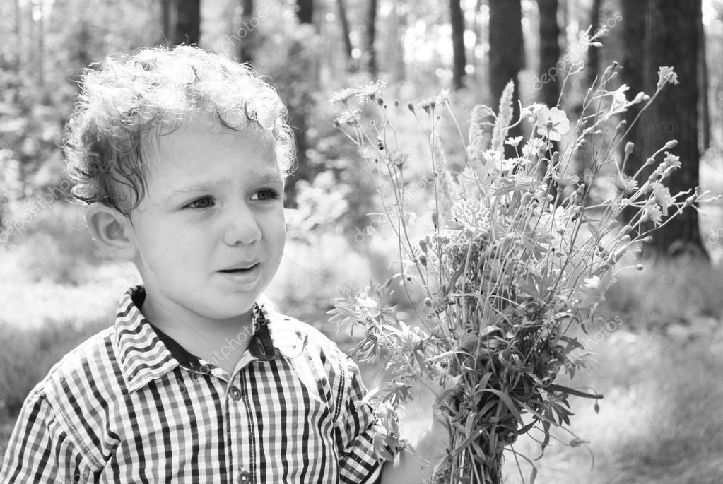 upset little boy with a bouquet of flowers