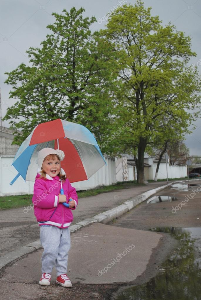 in the spring of a little girl standing under an umbrella on th