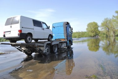 truck transports passenger car which appeared over the river ban