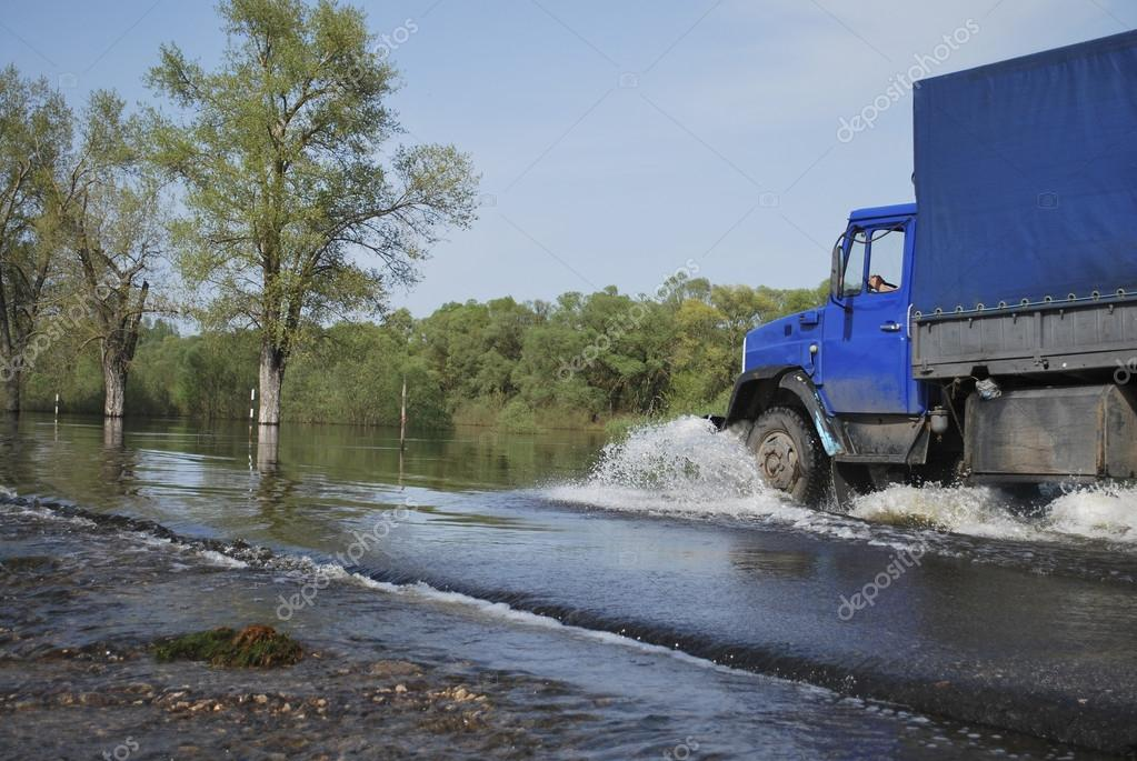 truck travels across the river which came out of its banks and f