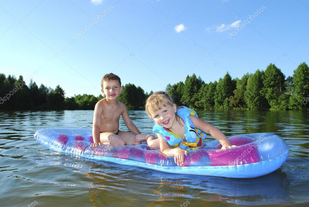 Summer on the river boy and girl floating on an air mattress.