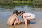 malé děti si hrají na pláži nedaleko jezera.