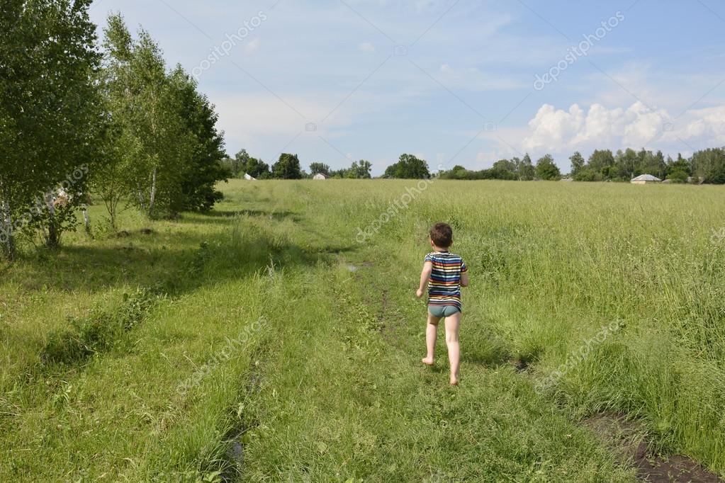 A village boy runs down the road in the field.