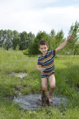 Barefoot boy runs through a puddle.