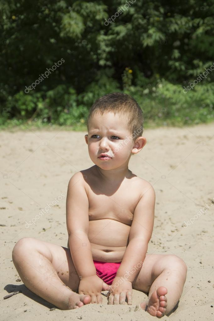 Little girl sits on a beach in the sand