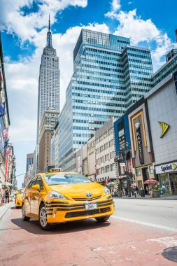Empire State building and yellow taxi cab on the street