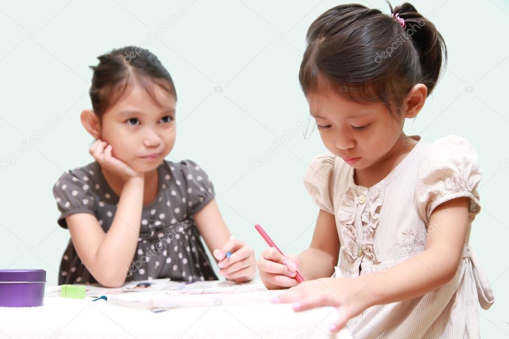 un niño femenino con cara aburrida mientras una hermana haciendo un ...