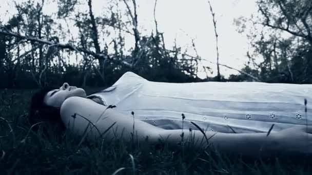 V bezvědomí žena ležící v trávě. Místo činu, hororové scény