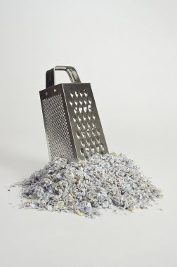 Cheese grater with paper shreds at the base