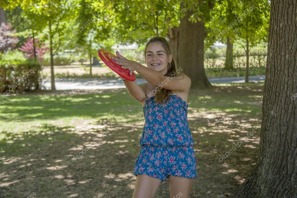 Young woman outdoor tossing a frisbee