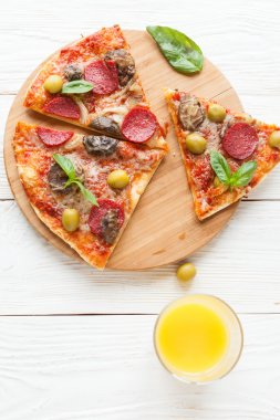 mouthwatering pizza with salami, cut into slices, top view