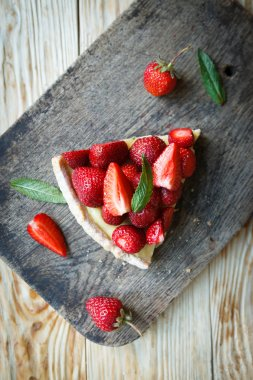 piece of tart with custard and strawberries