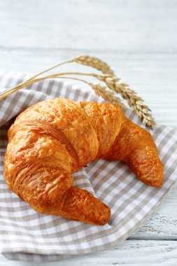 croissant and ears of wheat on a towel
