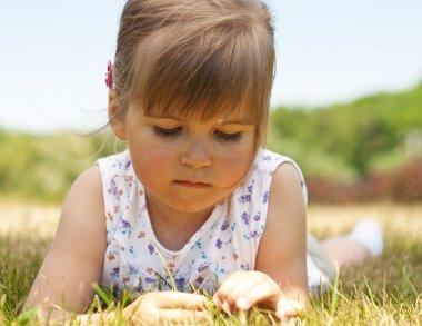 Little girl lying on grass in the park