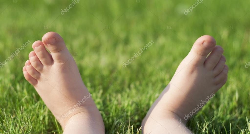 Child's barefeet on green grass