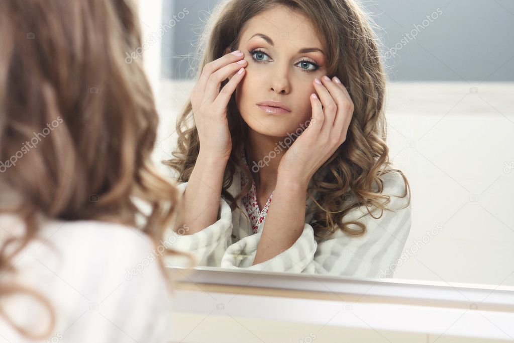 Young beautiful girl looks in the mirror