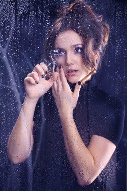Woman with eyelash curler for eyelashes
