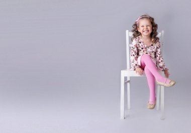 Cheerful little girl sitting on the chair with smile
