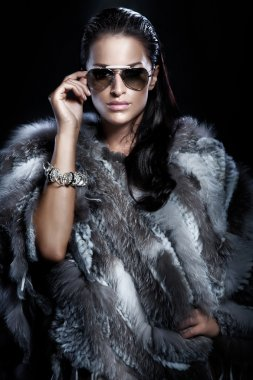Pretty woman wearing sunglasses and beautiful fur