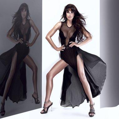 Fashionable young woman posing in long black dress
