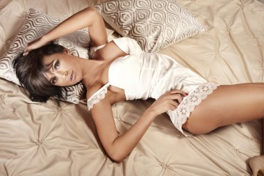 Sensual brunette woman relaxing in bed