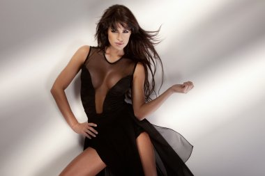 Attractive young sexy girl posing in black sensual dress