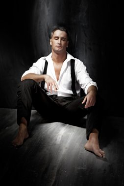 Photo of handsome tired businessman sitting on the floor, relaxi