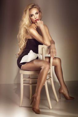 Beautiful luxurious blonde woman sitting on chair. Studio shot.