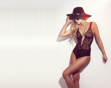 Sexy blond lady with perfect tanned body posing in black hat.
