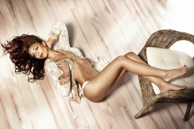 Attractive young brunette beauty relaxing in bright room.