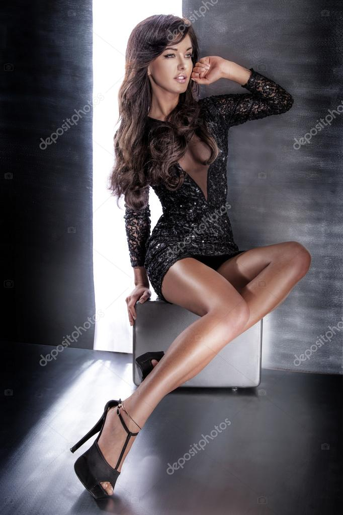 Attractive brunette woman sitting in elegant dress.