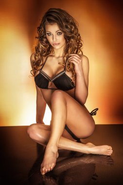 Attractive young brunette woman sitting and posing in underwear.