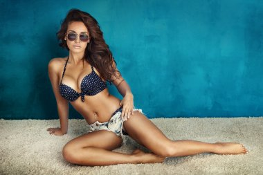 Tanned brunette lady posing in sunglasses.