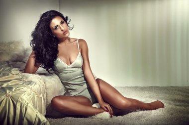 Sensual brunette woman in bedroom