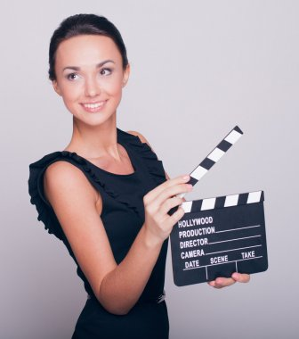 woman holds an open film slate
