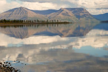 Lake Lama and reflected in the water clouds and mountains of the