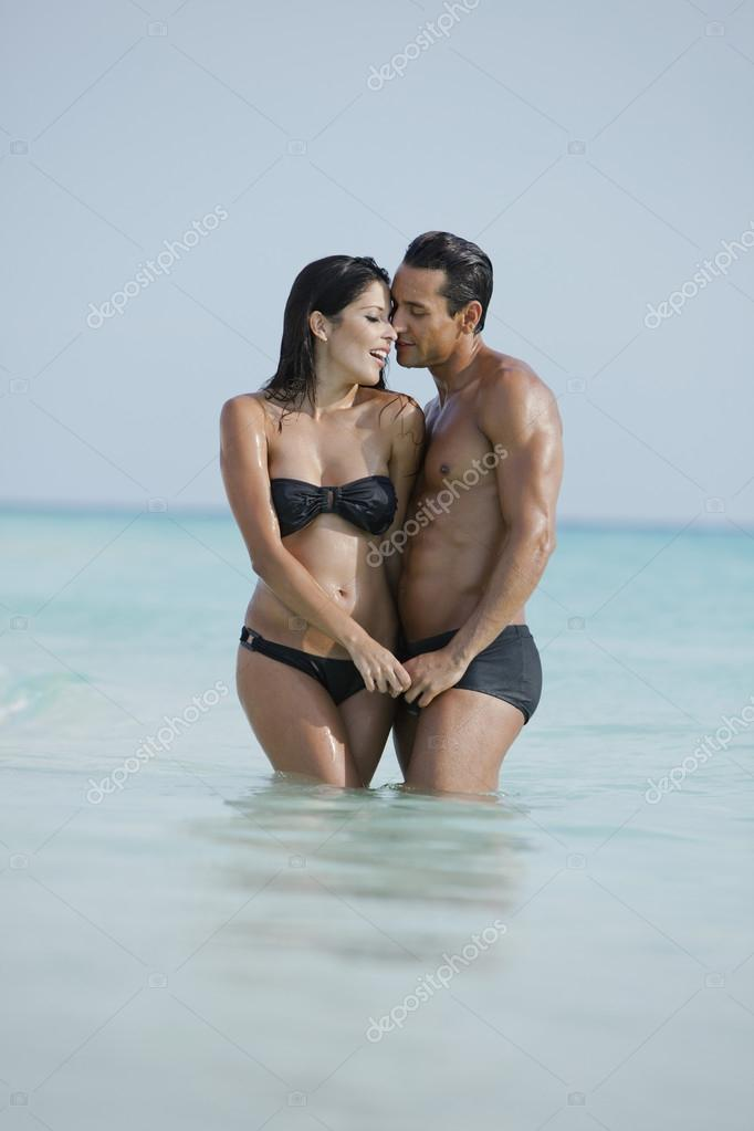 Couple romancing in water on the beach