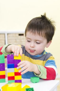Young boy plays with connecting bricks