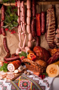 Sausages, pork, salami and vegetables background. Meat still life