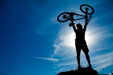 Silhouette of a man with a bike