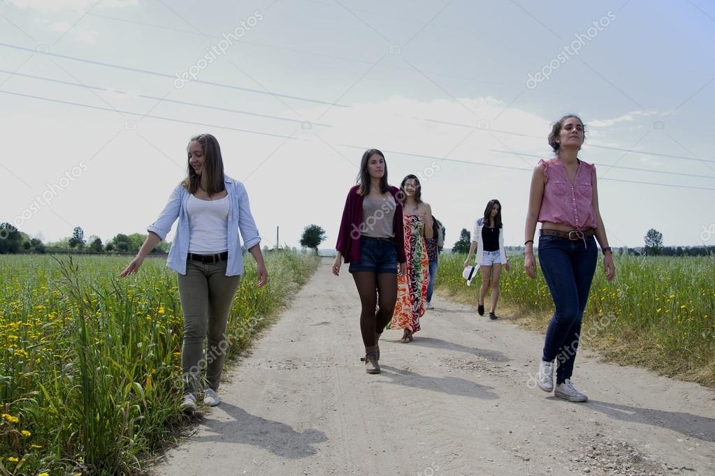 Group of young women walking on a field of wildflowers