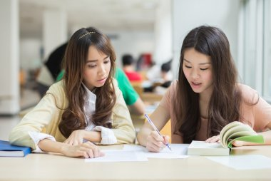 Asian students working in the library.