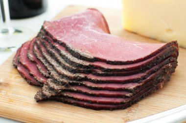 Deli pastrami meat sliced on cutting board