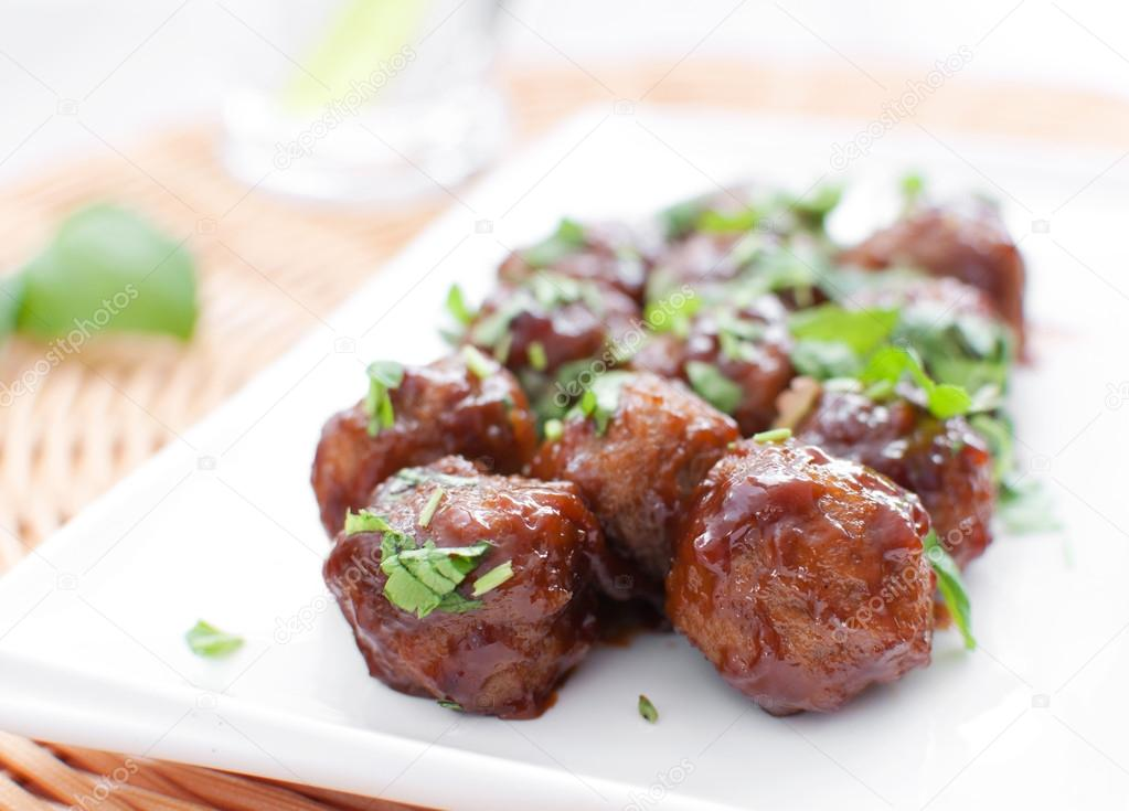 Plate of meatballs in gravy with herbs