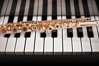 14k Rose gold flute on a piano keys
