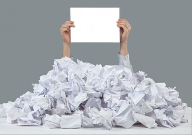 Hands with empty paper reaches out from big heap of crumpled papers