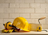 Fotografie brick background, helmet and measuring tape