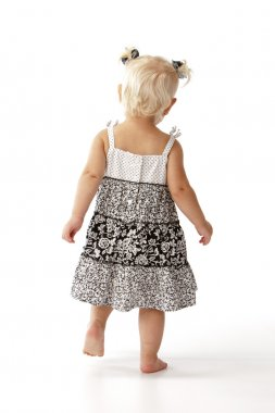 Full length caucasian toddler girl in dress walking away