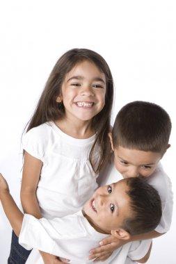 Smiling hispanic siblings hugging