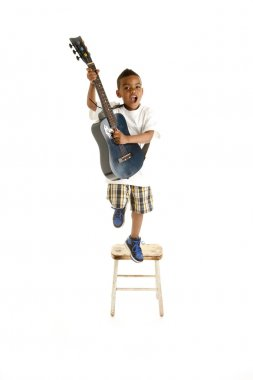 African american little boy performs a song with guitar